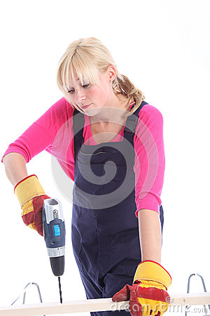 Woman drilling a hole in a plank of wood