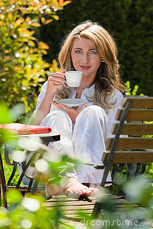 Woman drinking coffee breakfast in the garden