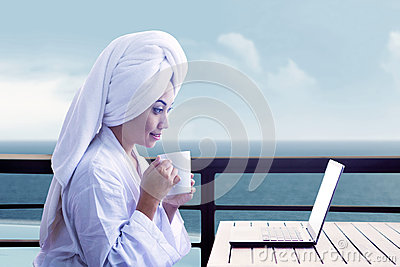 Woman drinking coffee by laptop