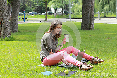 Woman Drinking Coffee in a Park