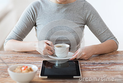 Woman drinking coffee and using tablet pc