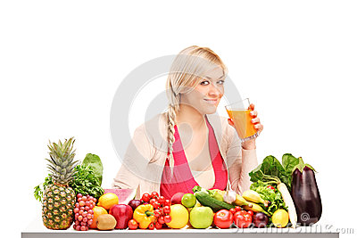 Woman drinking juice, on a table full of food
