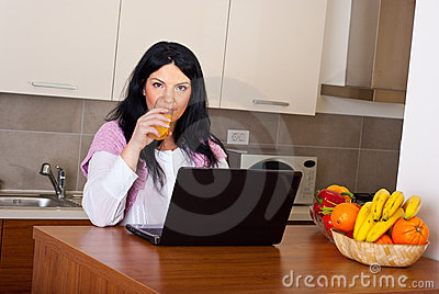 Woman drinking orange juice in kitchen
