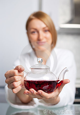 Woman drinking tea (focus of the teapot)