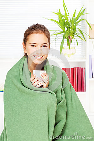 Woman drinking tea  at home covered with blanket