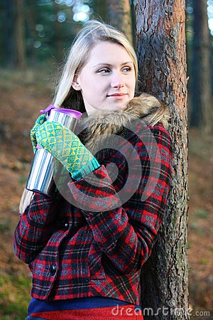 Woman drinking tea from a thermos cup