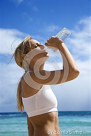 Woman drinking water on beach.