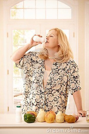 Woman drinking yogurt in kitchen