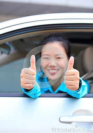 Woman driver thumb up in car
