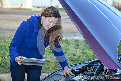 Woman a driver with touchpad repairing broken car