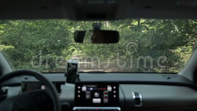 Woman driving car on ground road in the forest stock video