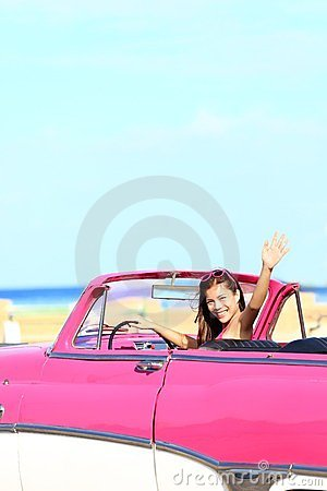 Woman driving convertible car waving happy