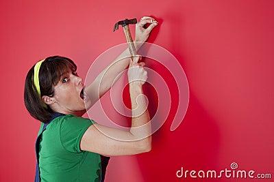 Woman driving a nail
