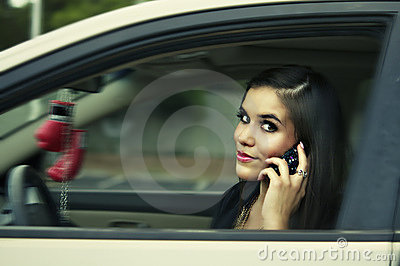 Woman driving to work holding cell phone.
