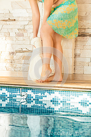Woman drying legs with towel at swimming pool
