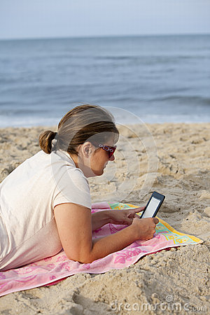 Woman with E-Reader at Beach