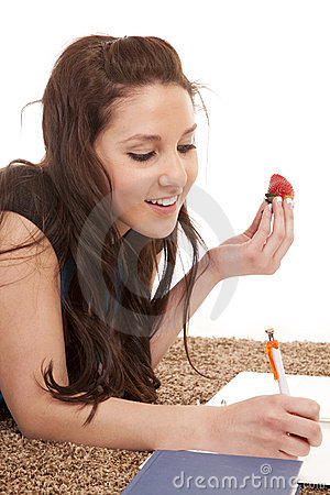 Woman eat strawberry homework writing.