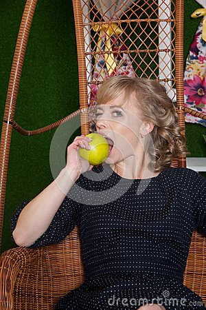 Free Woman Eating An Apple Sitting On A Chair Royalty Free Stock Photo - 55323795