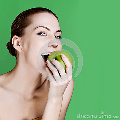 Woman eating apple smiling on green background.