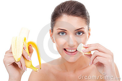 Woman eating banana and smiling