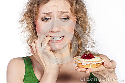 Woman eating a cake. In studio