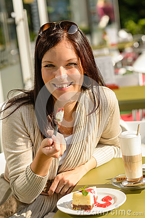 Woman eating cheesecake at cafe bar happy