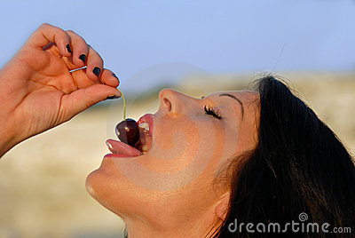Woman eating a cherry