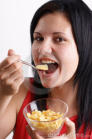 woman eating corn flakes from a bowl
