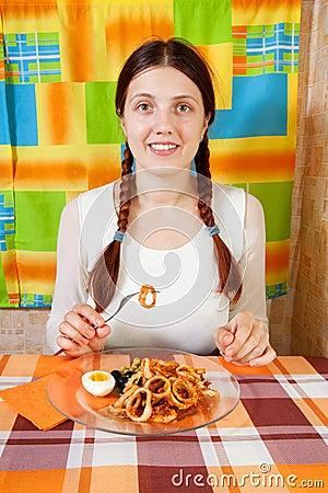 Woman eating  fried calamaries rings