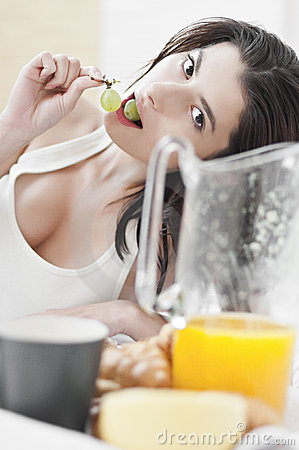 Woman eating grapes on breakfast