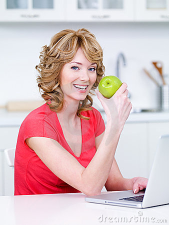 Free Woman Eating Green Apple In The Kitchen Stock Image - 14076981