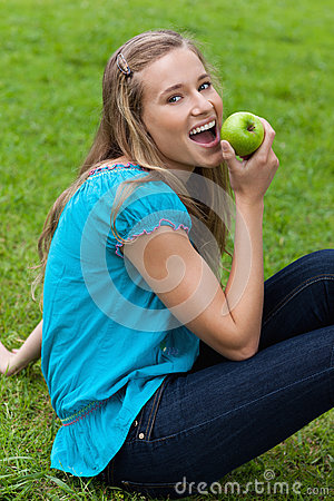 Woman eating a green apple while sitting in a park