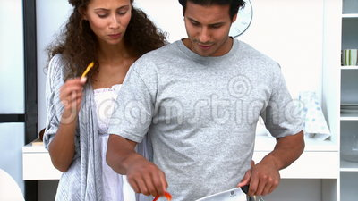 Woman eating while her husband is cooking vegetables Stock Photo