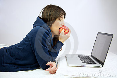 Woman eating red apple in front of computer
