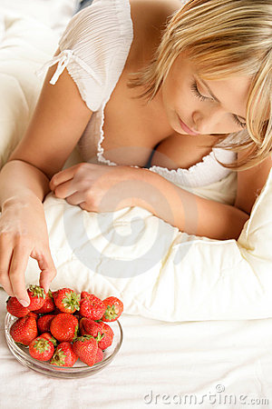 Woman eating strawberry with cream