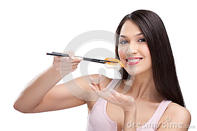 Woman eating sushi with a chopsticks