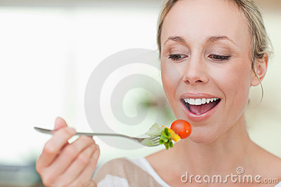 Woman eating a tomato