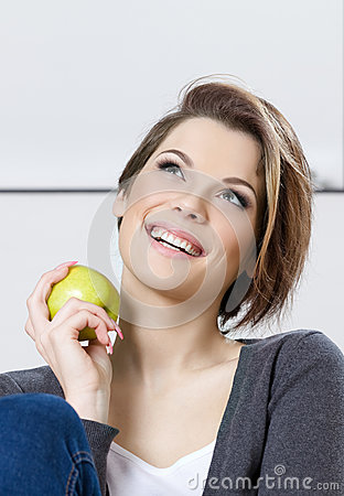 Woman eats a green apple