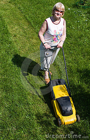 Woman with an electric mower at the cottage