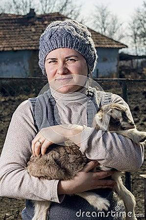 Woman embracing a goatling.