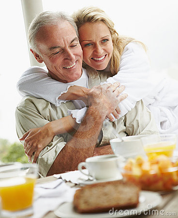Woman embracing her husband at breakfast table