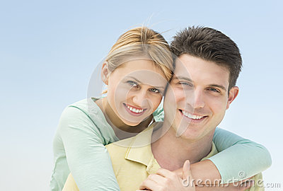 Woman Embracing Man From Behind Against Clear Blue Sky