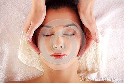 Woman enjoy receiving face massage at spa saloon