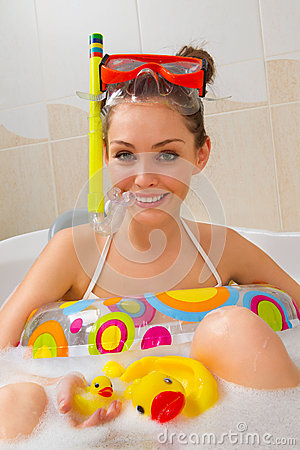 Woman is enjoying a bath in mask with snorkel.