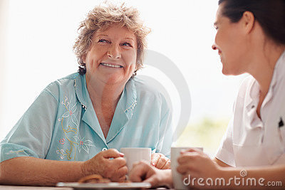 Woman enjoying a cup of coffee with a nurse