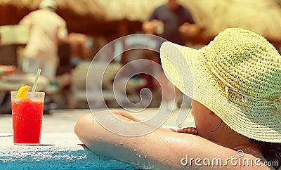 Woman enjoying drink at swimming pool
