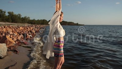 Woman enjoying freedom and life on beach at sunset stock footage