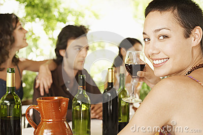 Woman Enjoying Red Wine With Friends In Background