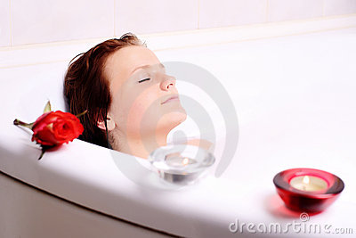 Woman enjoys the bath-foam in the bathtub.
