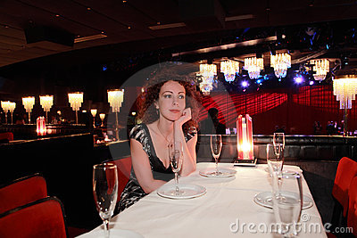 Woman in evening dress sitting at table